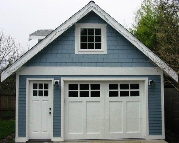 white craftsman style garage door on blue house