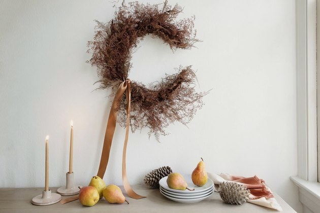 DIY crescent moon shaped dried floral wreath on wall above table with pears, plates and candles