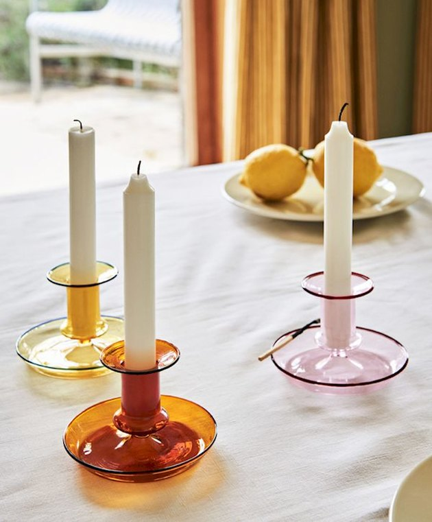 white candlestick in colorful candle holders on white tablecloth