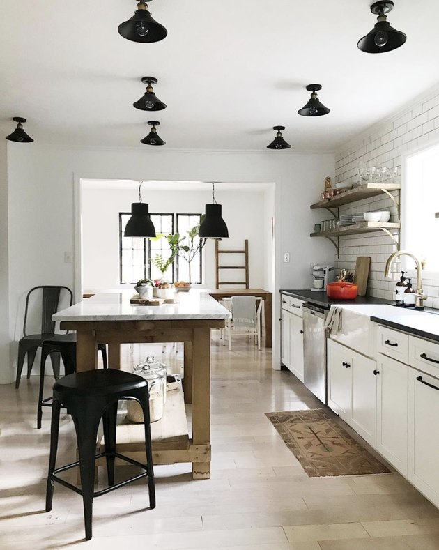 House Seven Design white kitchen with black ceiling lights and marble-topped island