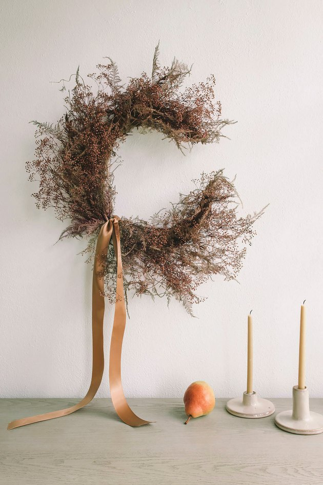DIY crescent moon wreath with dried florals hung on wall above table with candles and pear