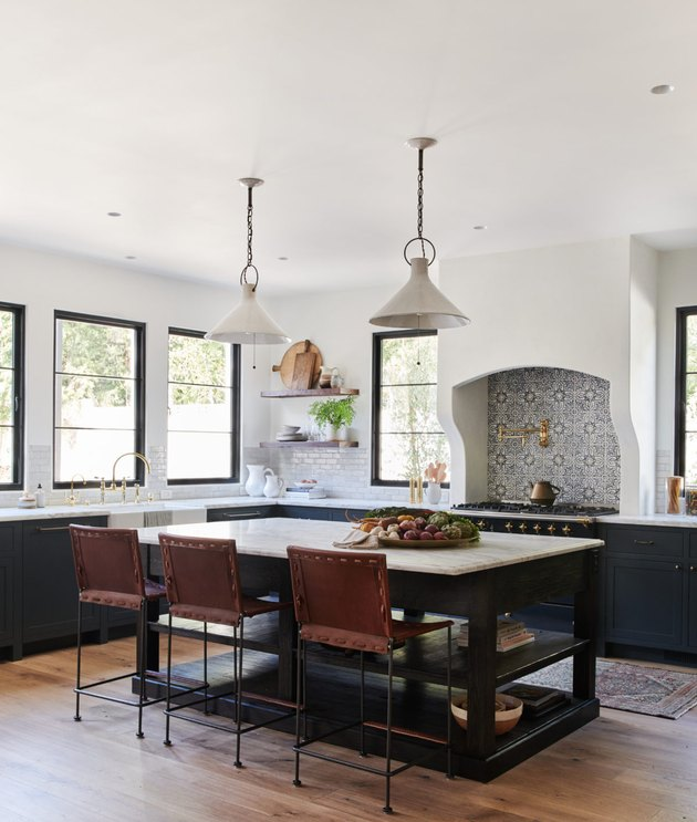 kitchen island idea in farmhouse kitchen with black cabinets and pendants over island with patterned tile backsplash