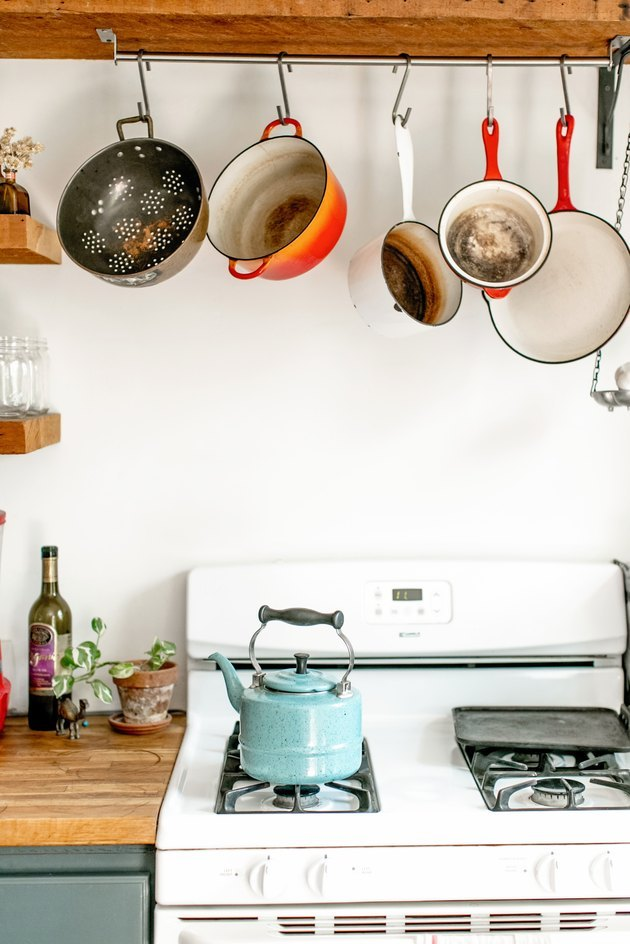 kitchen idea with wood countertops and hanging pots and pans over white appliances