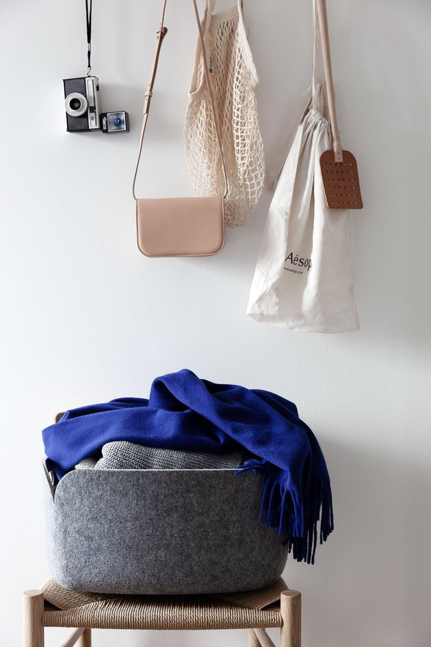 bedroom closet idea with accessories hanging from wall hooks and clothes folded in basket