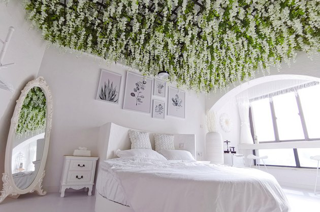 white bedroom with flowers hanging from ceiling