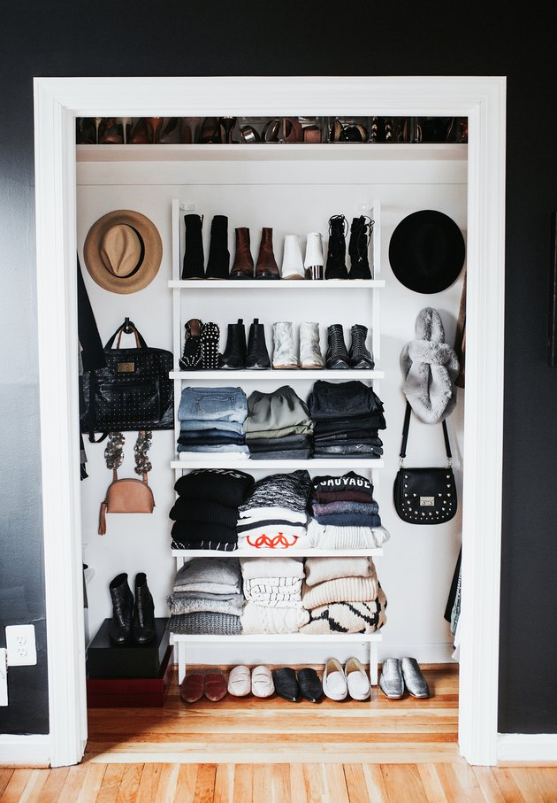 Reach-In bedroom closet idea by Meg Biram with open shelving and wall hooks