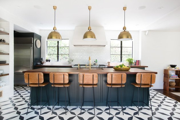 kitchen idea with brass pendants over island with wood countertop and blue cabinets