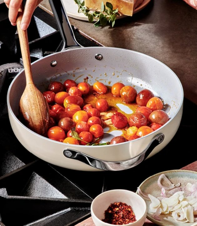 White ceramic pans with tomatoes on cooktop.