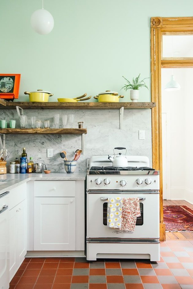 mint green kitchen with retro stove and checkered tiles