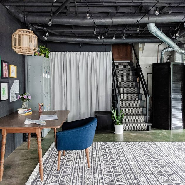 Black garage office with patterned rug and desk with blue chair
