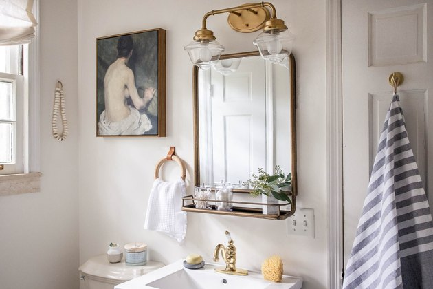 Bathroom with brass mirror, brass light fixture, striped towel, and painting.