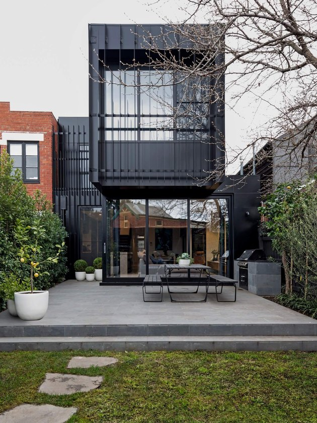 black contemporary home exterior idea with outdoor seating