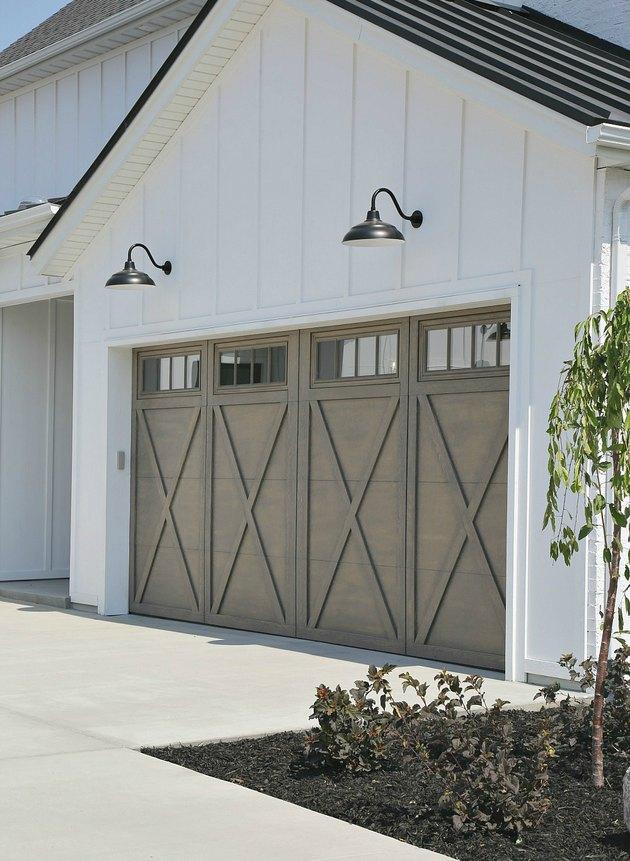 Light gray wood barn garage doors with X design and barn lights