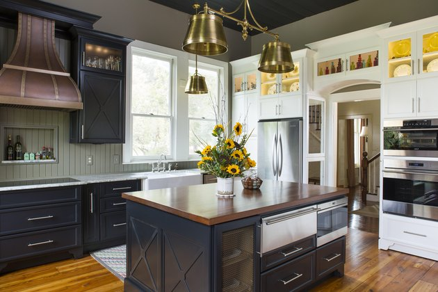 Modern farmhouse kitchen with dark cabinets and steel hardware, gray shiplap, white countertop, rustic wood oven hood, wall of white cabinetry, and light hardwood floors