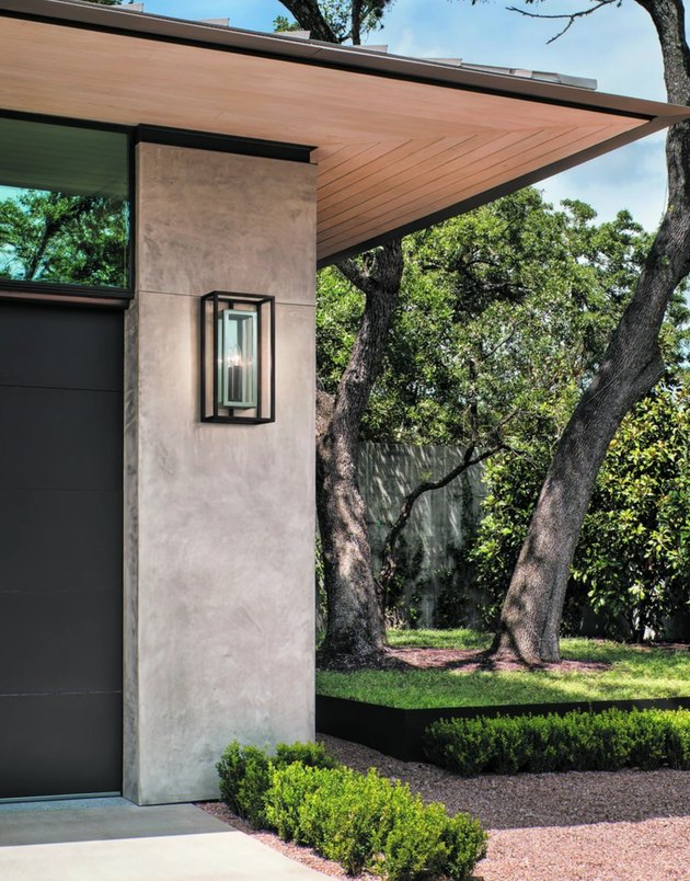 Contemporary home exterior with modern outdoor sconce and black garage door