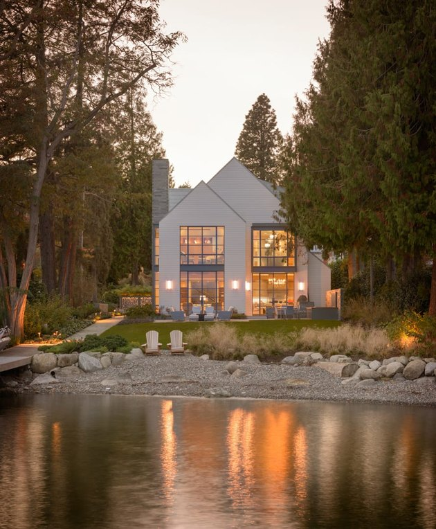 Contemporary home exterior next to lake with large windows