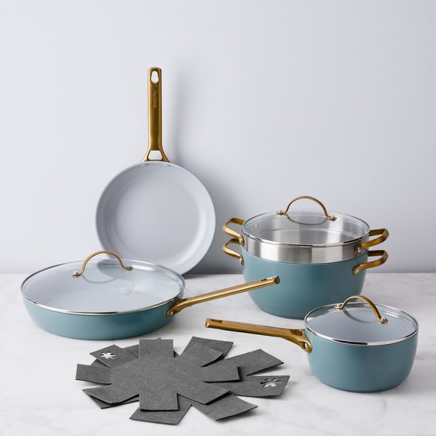 Teal ceramic cookware set with brass handles