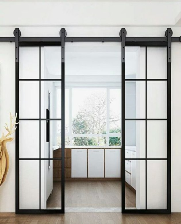 Glass and metal Contemporary Barn Doors leading into modern kitchen.