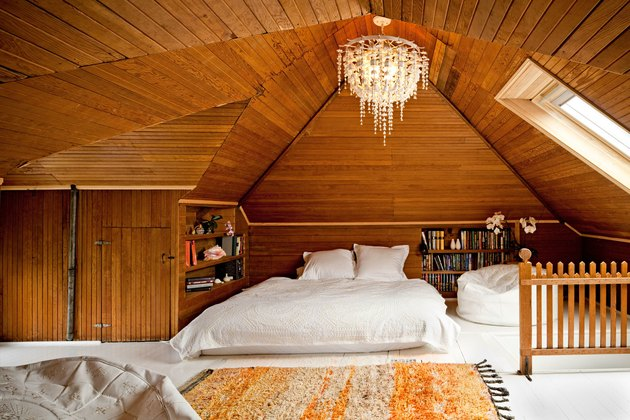 wood-clad walled bedroom with chandelier for bonus room above garage idea