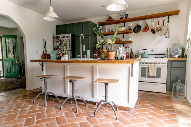 Mexican tile floor in kitchen with green cabinets and wood countertop