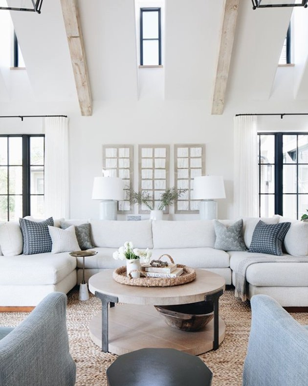 living room sectional with white sofa and back cushions and blue throw pillows