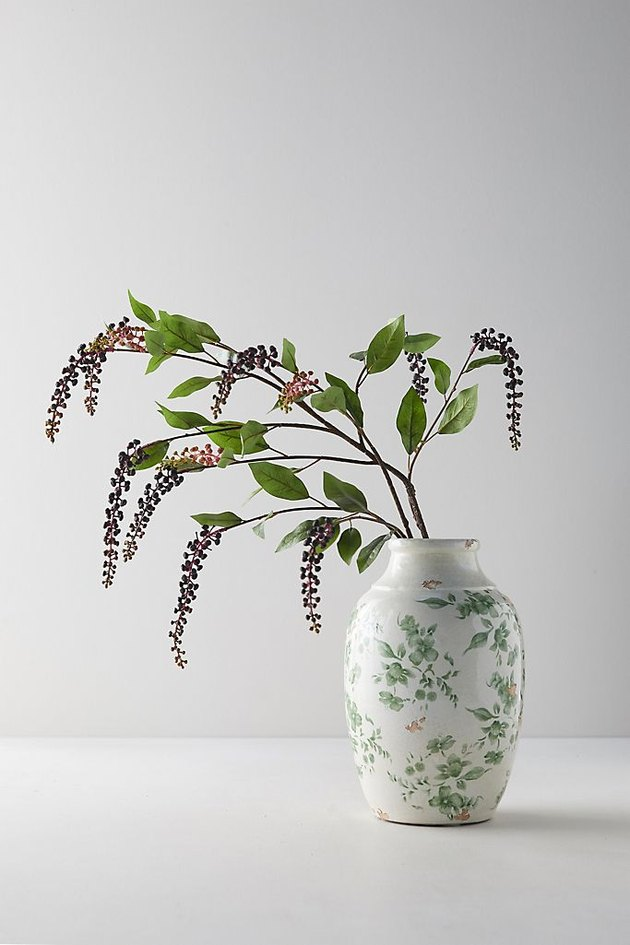 white backdrop with vase of winter berries for Christmas decorations list
