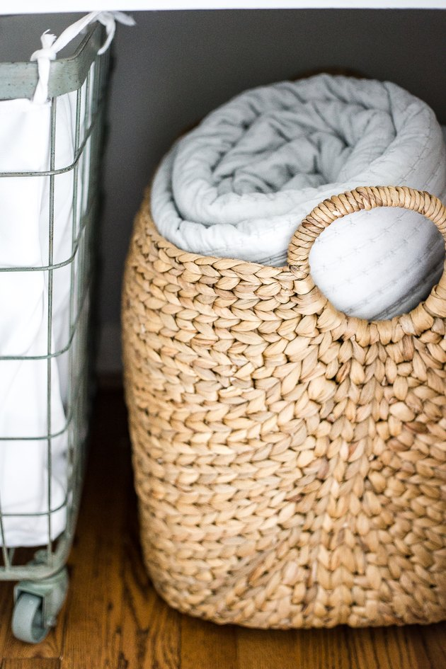 linen closet organization with hamper on wheels and basket with blanket