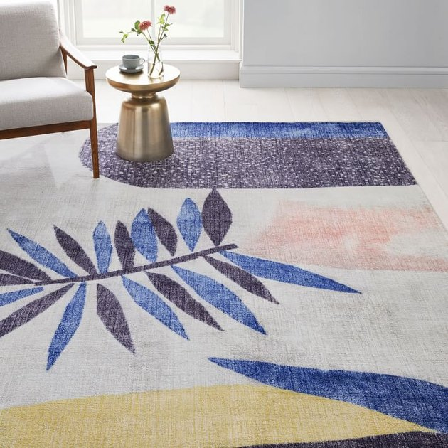 abstract cream rug with blue, yellow, and pink accents