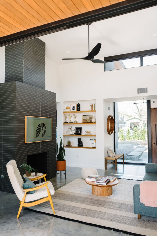 Midcentury living room style with black tile fireplace surround and concrete flooring