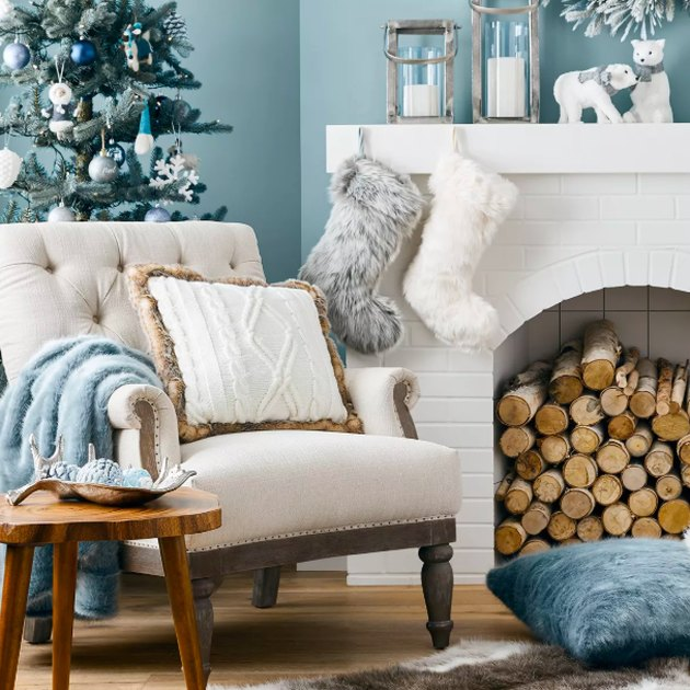 tree with ornaments and white chair and white fireplace nearby with holiday decor