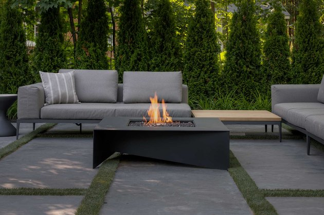 Black contemporary fire pit on outdoor patio next to seating