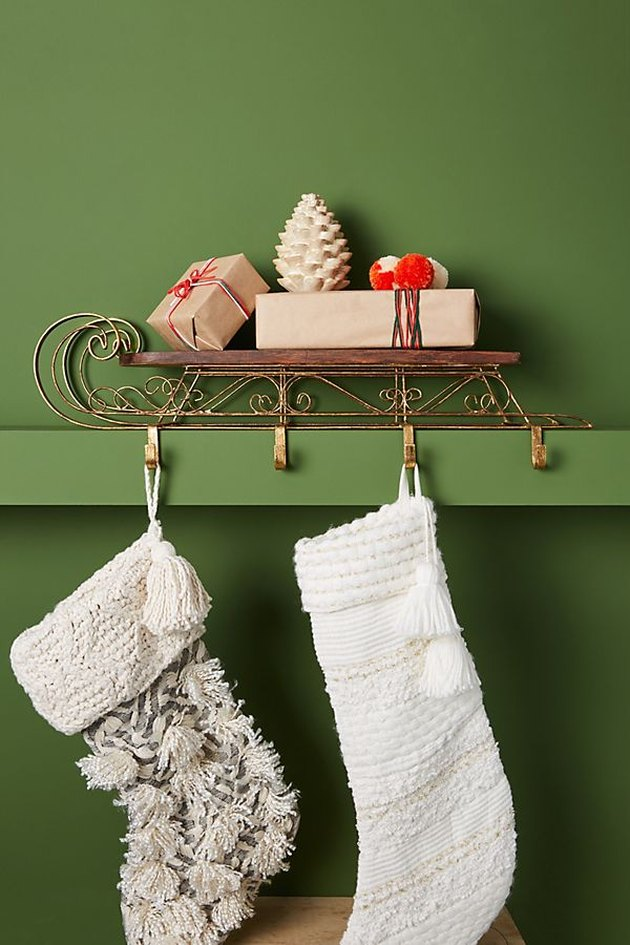 green wall with sled ornament and hanging stockings