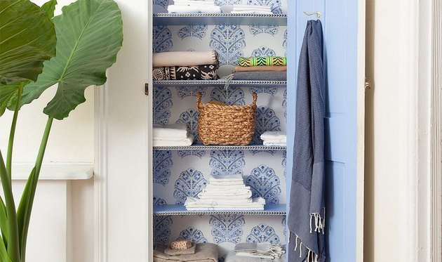 linen closet organization with wallpaper on back wall and painted door