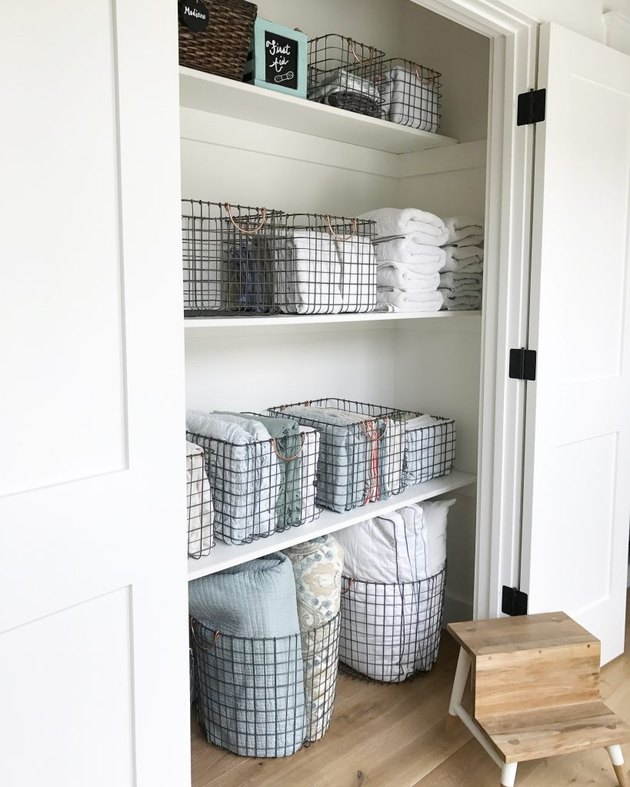 linen closet organization with wire baskets and bins filled with linens