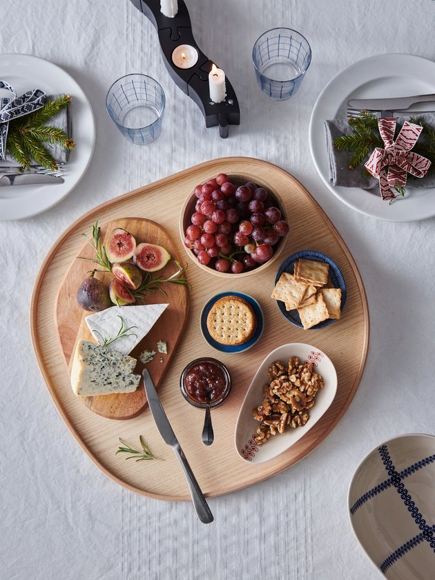overhead view of table with cheese board and candles