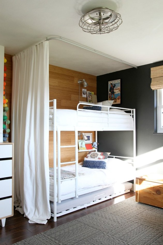 bedroom with white bunk beds and black accent wall