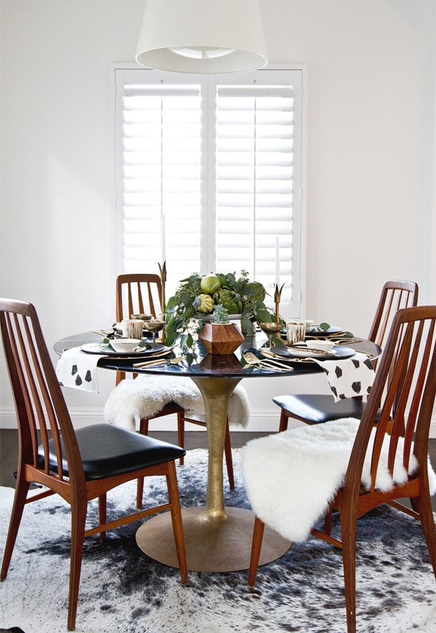 dining room with sheepskin throws on chairs and produce centerpiece