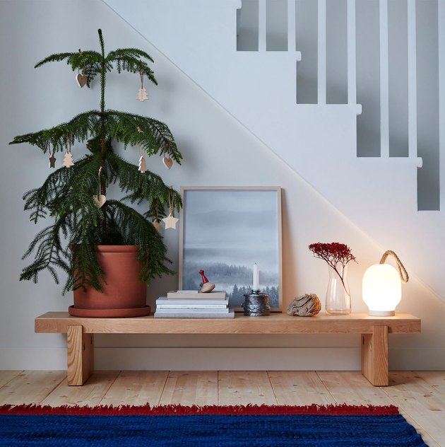 wooden bench with christmas tree and decor near stairs