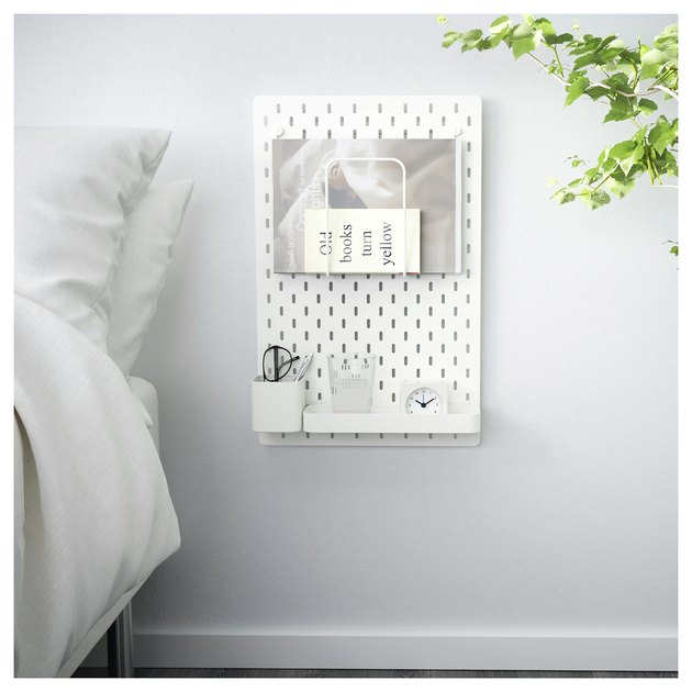 A pegboard beside a bed