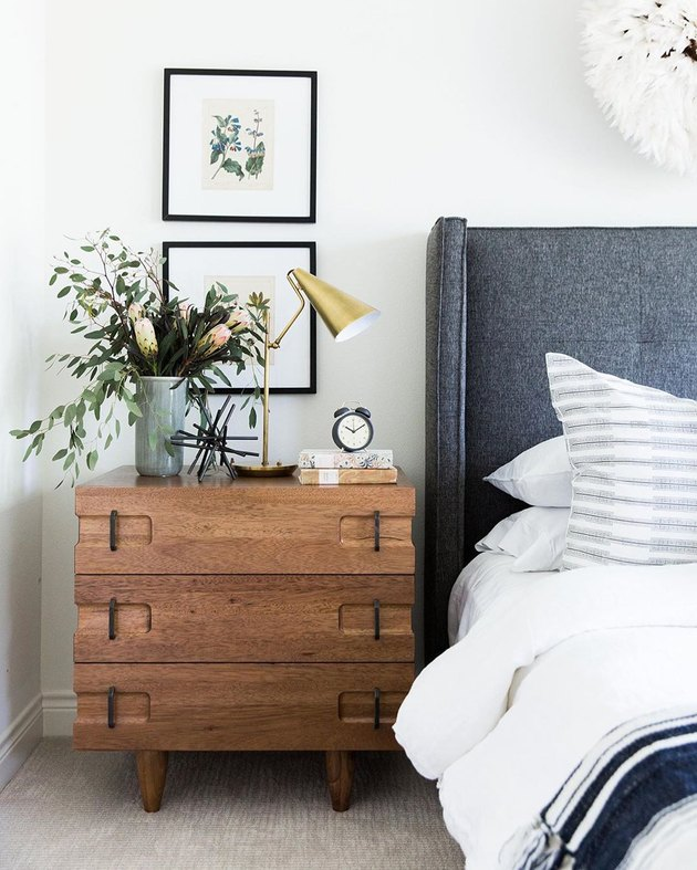 midcentury bedroom lighting idea with table lamp on wood nightstand next to upholstered headboard