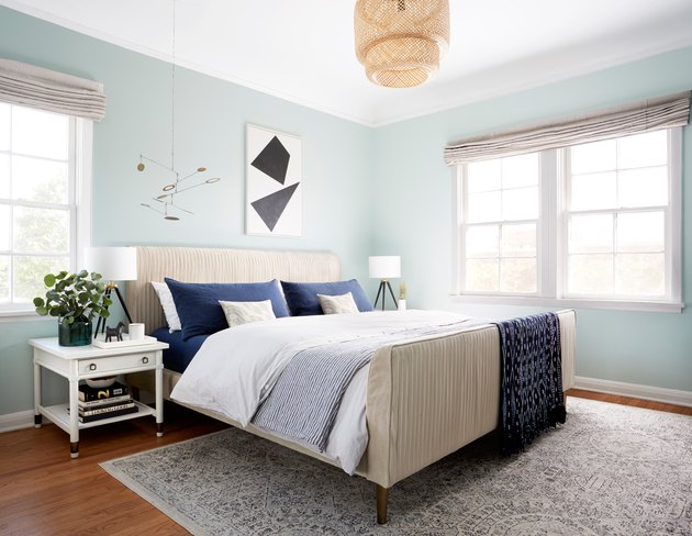 midcentury bedroom lighting idea with woven pendant above bed