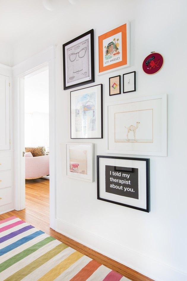 hallway with rainbow rug and framed prints on the wall