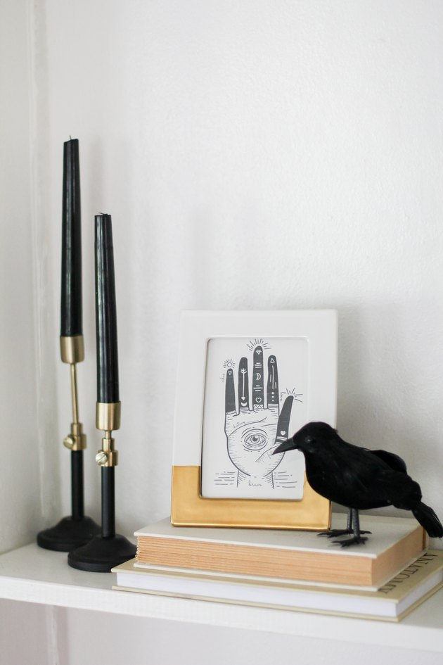Black and gold candlesticks, white and gold frame with palmistry print, and a crow