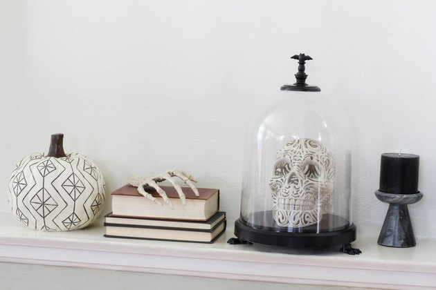 Etched white pumpkin, books, skeletal hand, skull in cloche