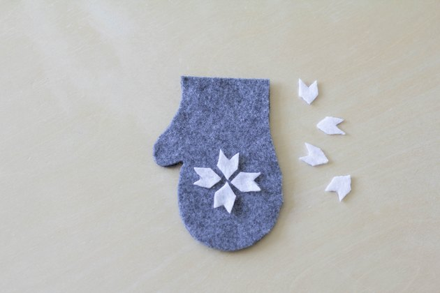 Gluing felt snowflake on top of mitten