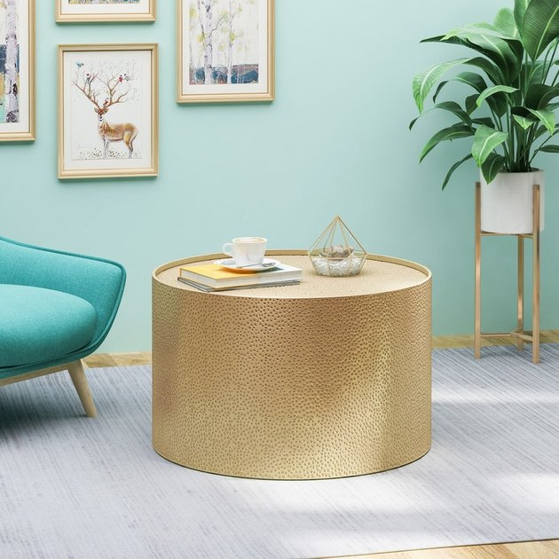 gold round coffee table with light blue background