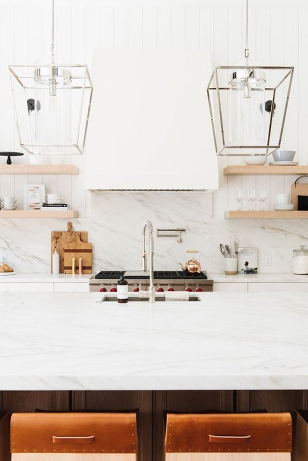 white marble chef's kitchen with gooseneck kitchen faucet with undermount kitchen sink and pot filler at stove