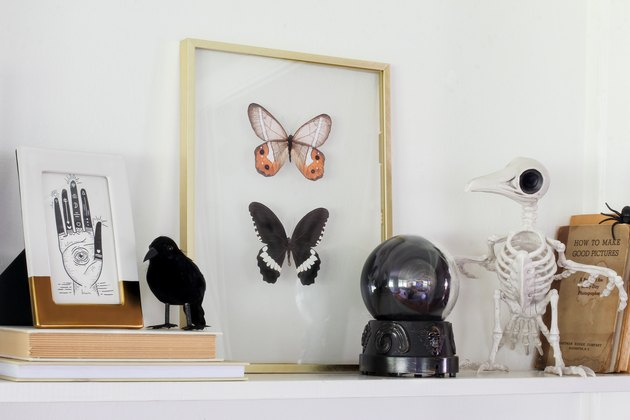 Brass float frame with butterflies, crystal ball, crow skeleton
