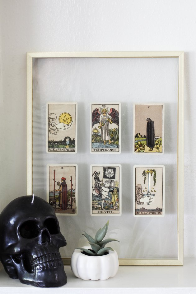 Black skull candle, pumpkin succulent planter, and brass float frame with tarot cards