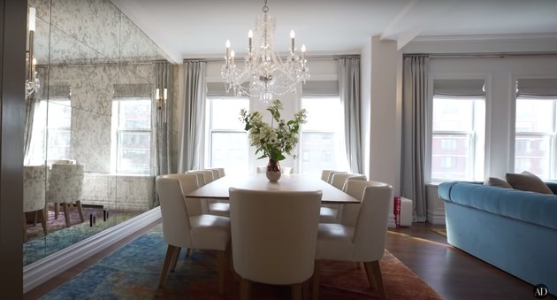 misty copeland dining room featuring chandelier, white chairs, and textured mirror wall
